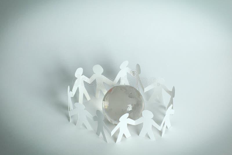 combine a los hombres de papel que se colocan alrededor del globo de cristal fotos de archivo