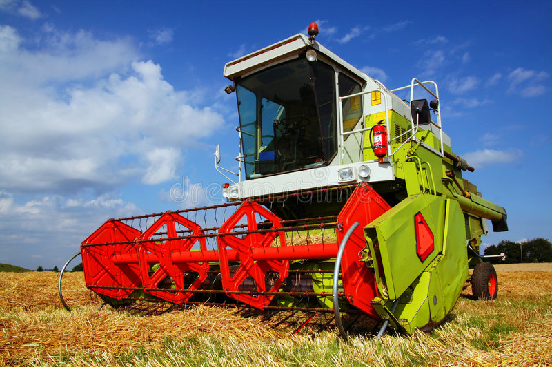 Combined harvester. In field. Agriculture harvest machine in red and green against blue skye stock photography