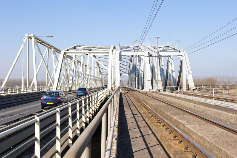 Combined railway and car bridge over river. Historical Dutch bridge with separated railway and car lanes crossing the river IJssel at the city Westervoort, the royalty free stock image