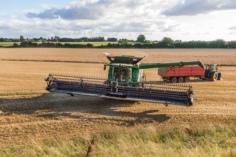 Combineer machine en een tractor wacht stock fotografie