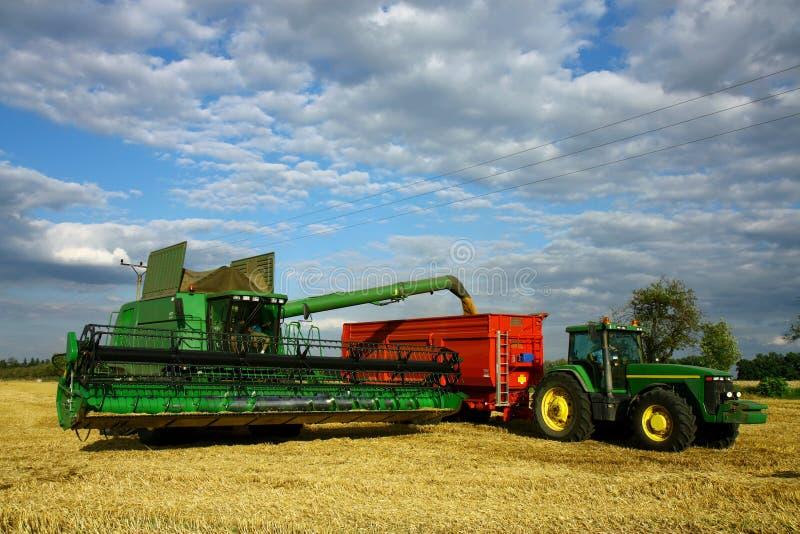 Combineer machine en tractor met aanhangwagen stock fotografie