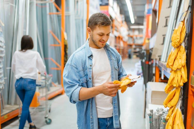 Combineer met handschoenen voor winkelen in hardware stock afbeelding