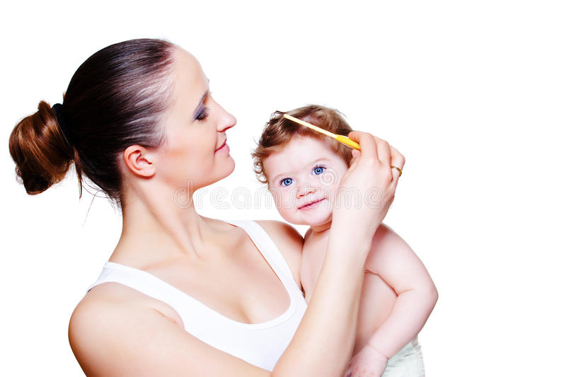 Combing baby hair. Loving mother combing baby hair stock photos