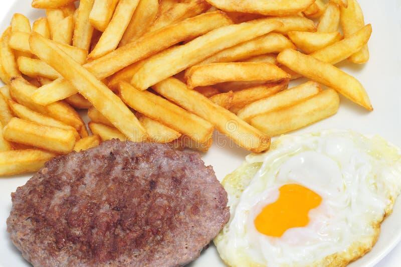 Combo uppläggningsfat med stekte ägg-, hamburgare- och fransmansmåfiskar royaltyfri fotografi