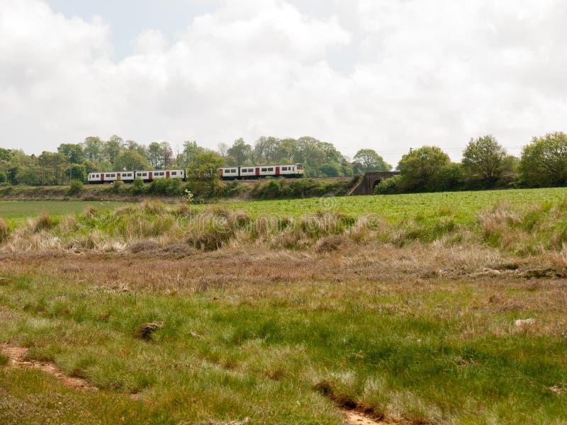 comboio que atravessa a paisagem rural no fundo da via imagens de stock royalty free