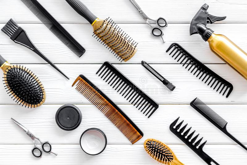 Combs, sciccors and hairdresser tools in beauty salon work desk on white wooden background top view pattern. Hair style concept. Combs, sciccors and hairdresser royalty free stock image