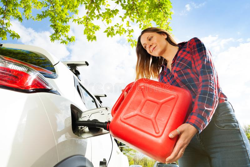 Combustível de derramamento da mulher no tanque de gás de um carro da lata fotos de stock royalty free