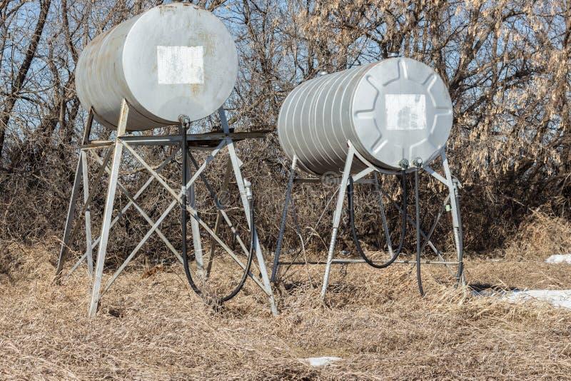 Combustível e depósito de combustível redondos velhos do metal dois com mangueira e bocal foto de stock