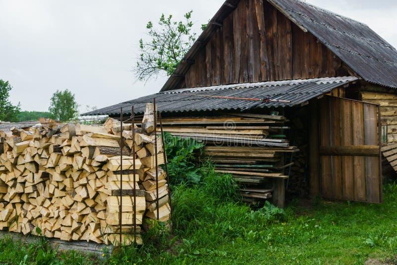 Combustível para o fogão que aquecem-se em casa e o banho Vida rural A lenha de madeira é colocada nas paredes Madeira natural fotos de stock