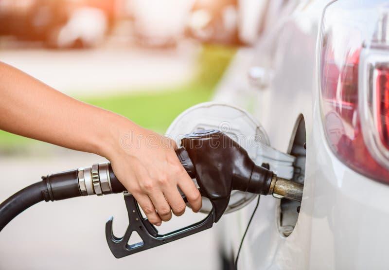 Combustibile di pompaggio della benzina della donna in automobile alla stazione di servizio fotografie stock