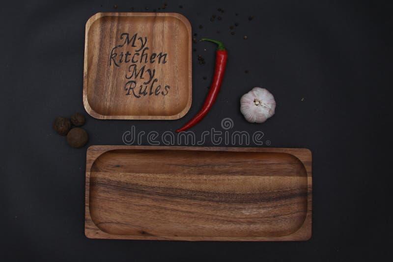 Combustion d'un plat en bois sur un fond d'ail noir et de poivron rouge chaud photo stock