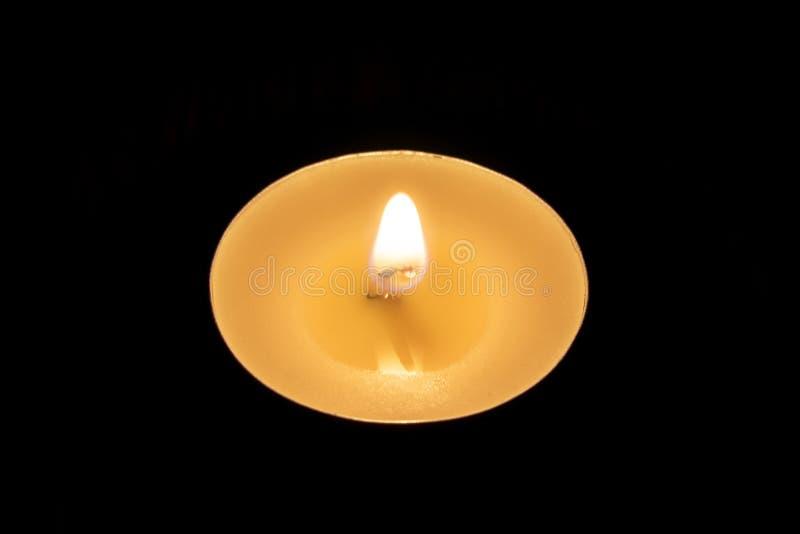 Combustione della candela nei precedenti neri immagini stock