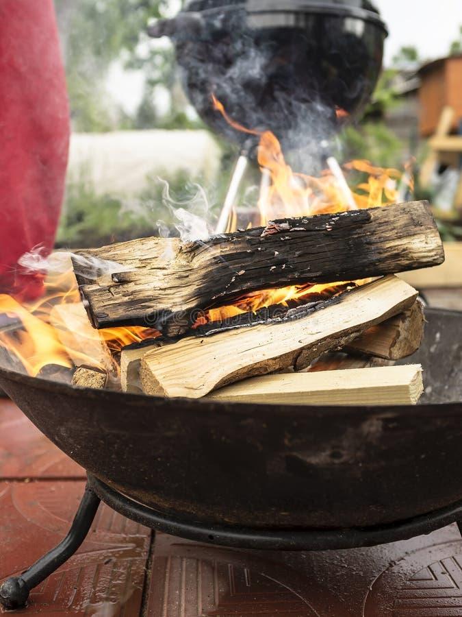 Combustione di legno nella ciotola del fuoco di accampamento per preparare i carboni per la griglia immagini stock libere da diritti