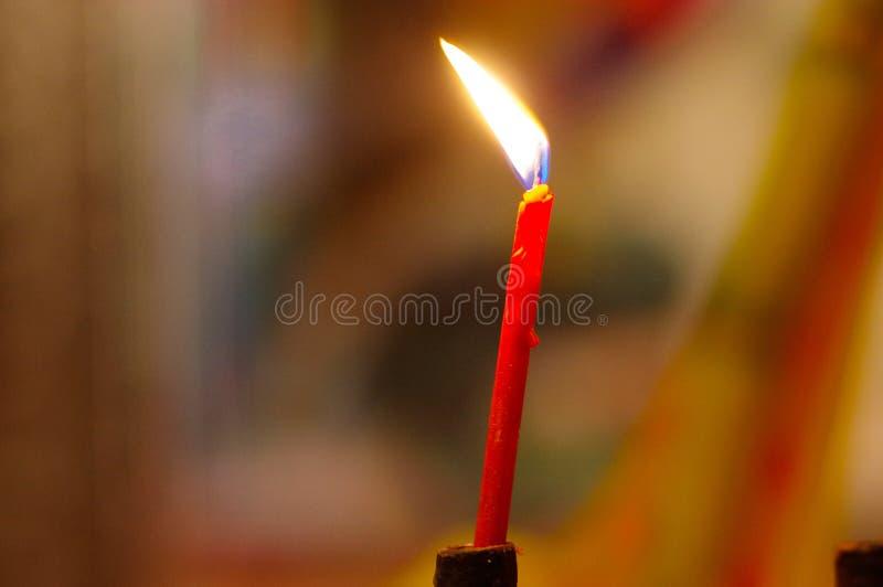Combustione rossa, candele lunghe in tempio di budist fotografie stock
