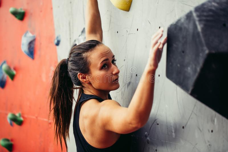Beautiful young strong woman climbing on red artificial wall top view. stock photo