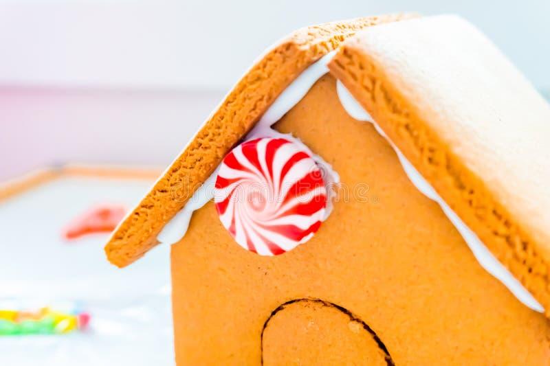 Começando a decorar uma verdadeira casa de pão de gengibre, com um círculo doce de cana doce, num telhado de biscoito mantido jun imagem de stock royalty free