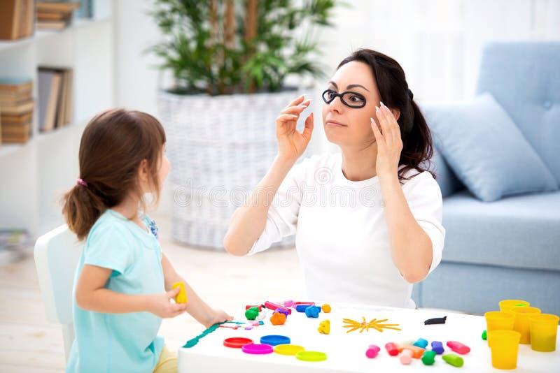 Come conservare vista sana La mamma e la figlia fanno i vetri da plasticine immagine stock