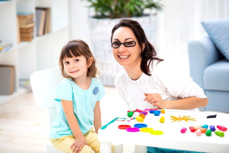 Come conservare vista sana La mamma e la figlia fanno i vetri da plasticine immagini stock