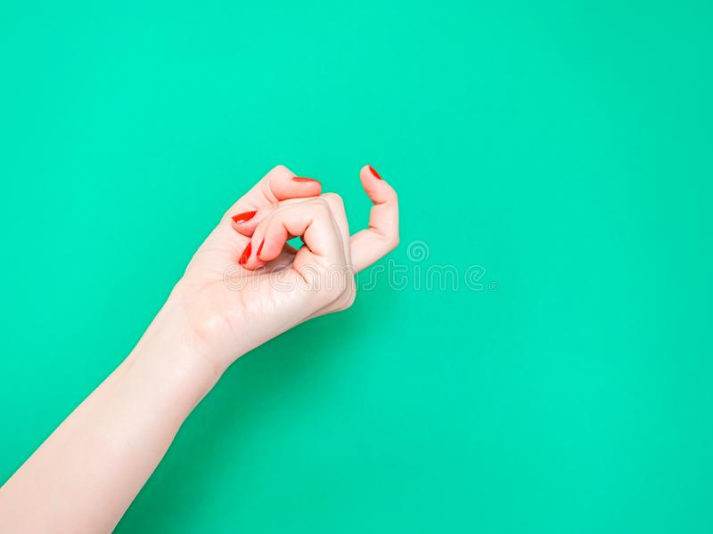 The Come Hither Hand Sign. Woman hand beckoning on isolated turquoise green color background. Female hand beckoning. Isolated on white background. Woman royalty free stock photography