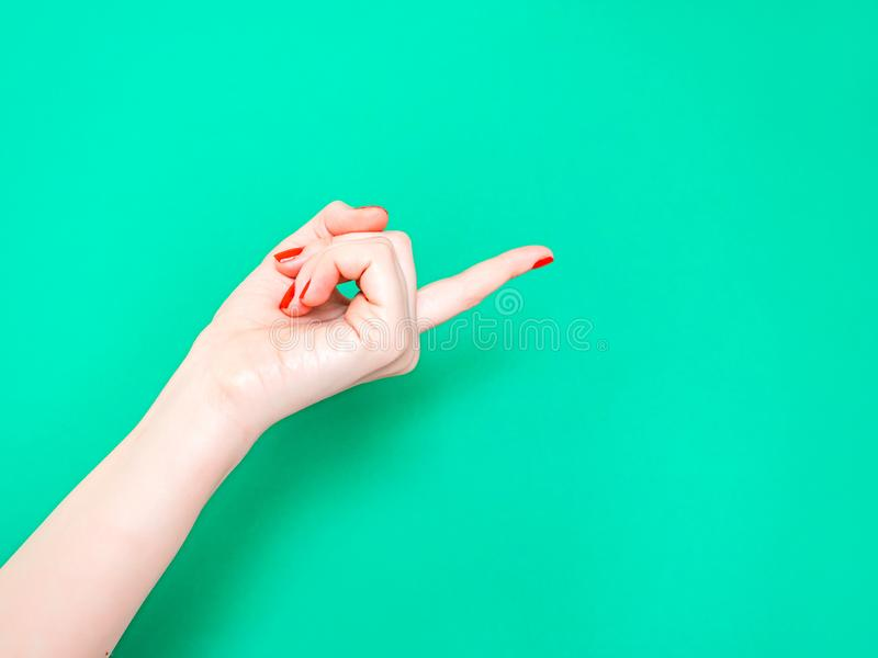 The Come Hither Hand Sign. Woman hand beckoning on isolated turquoise green color background. Female hand beckoning. Isolated on white background. Woman royalty free stock photo