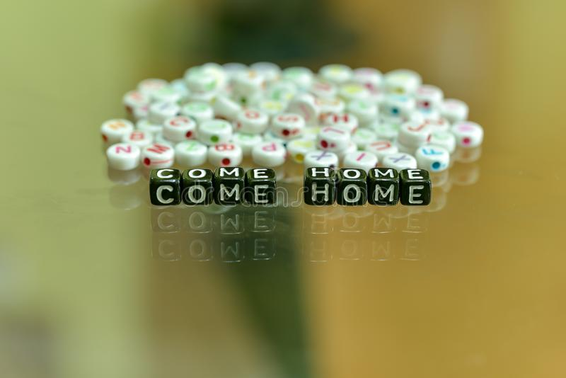 COME HOME  written with Acrylic Black cube with white Alphabet Beads on the Glass Background.  royalty free stock photo