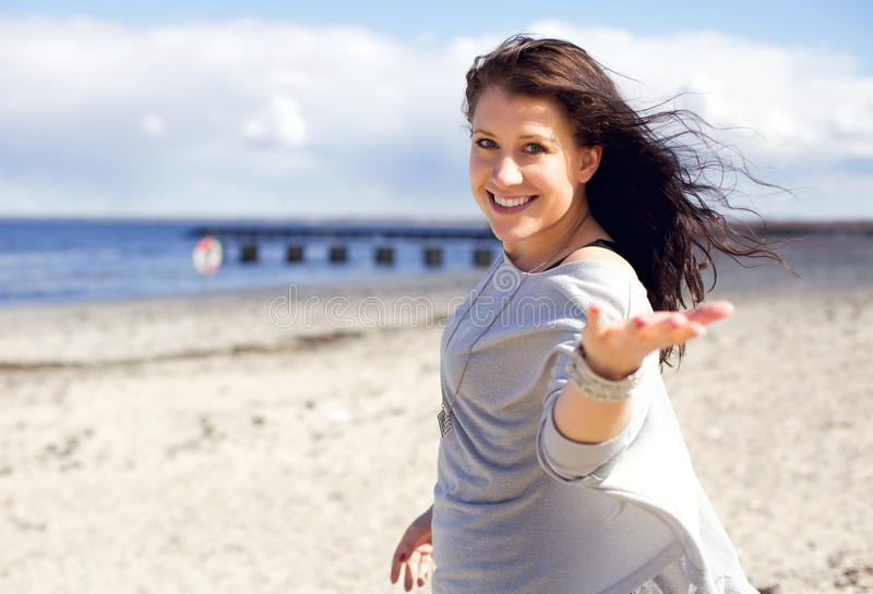 Come With Me. Woman walking on a beach in sunlight inviting you to come walk with her royalty free stock photo