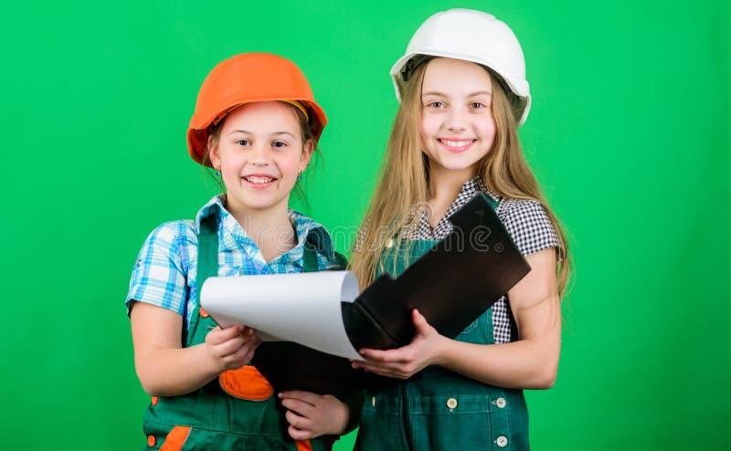 Come posso aiutilo piccole ragazze che riparano insieme nell'officina Ispettore del caporeparto riparazione Festa del Lavoro 1? M fotografia stock libera da diritti