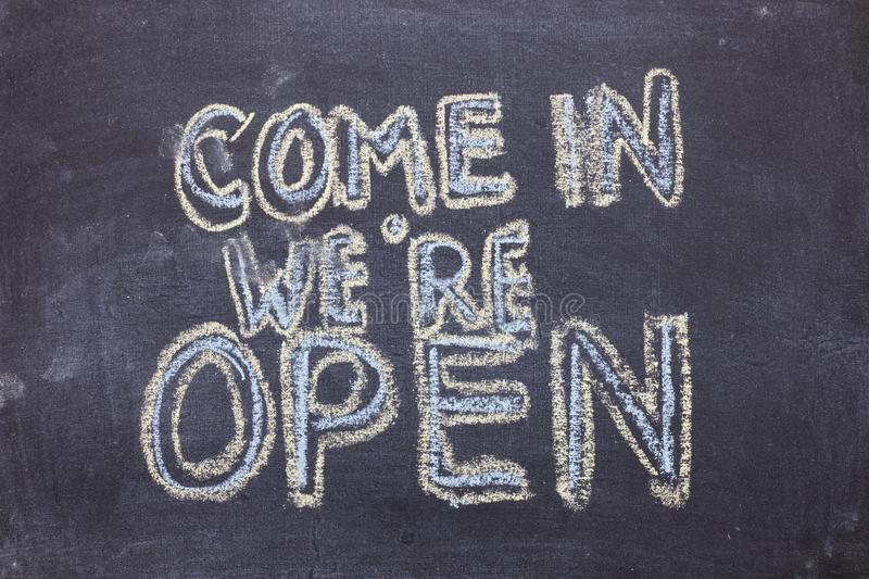 Come in we`re open. Chalk lettering on blackboard. Multi colored inscription royalty free stock images