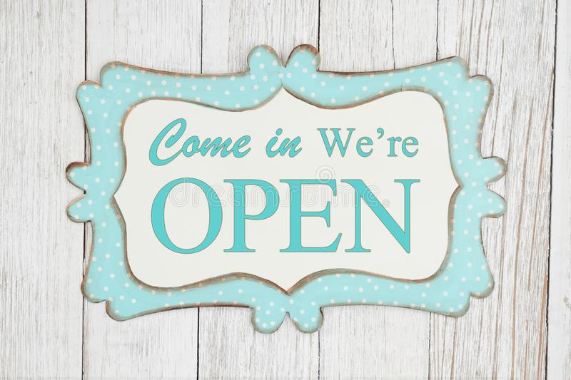 Come in we`re open text on a retro tin polka dot picture sign. On weathered whitewash textured wood vector illustration