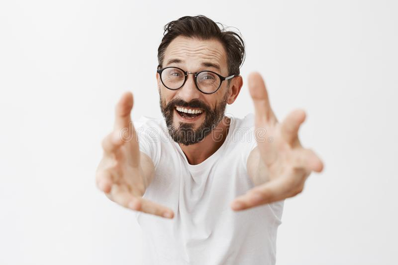 Come to me dear. Portrait of charming thrilled and happy mature male model with beard in trendy glasses and casual t stock photography