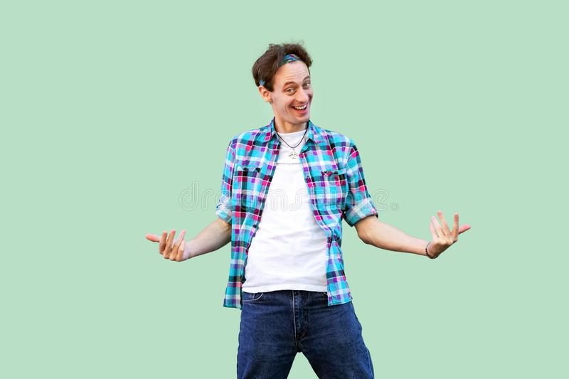 Come to me. Portrait of funny young man in casual blue checkered shirt and headband standing looking at camera and inviting to royalty free stock image