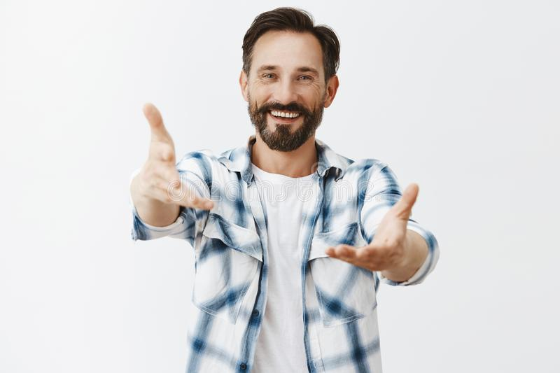 Come to papa. Portrait of friendly-looking kind and handsome father with beard and moustache, reaching palms towards royalty free stock photography