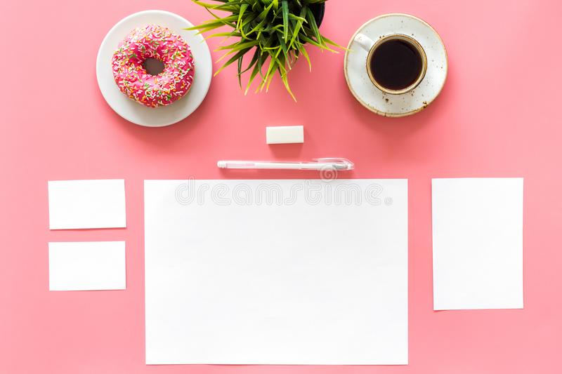Come up with brand identity. Blank stationery for branding near coffee and donut on pink background top view mockup royalty free stock photo