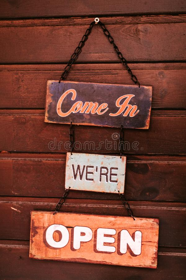 `Come in` Vintage open sign on wooden wall stock image