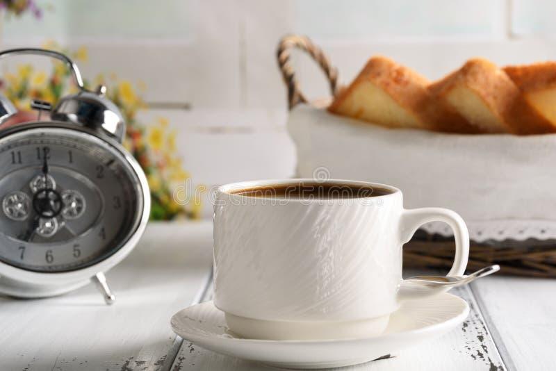 Comece acima o conceito Copo de café, despertador e brinde na cesta começo do dia do café da manhã imagens de stock
