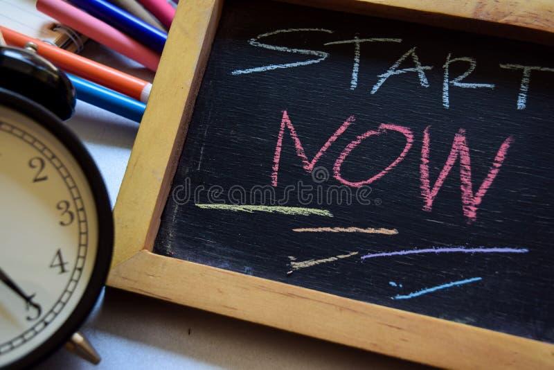 Comece agora escrito à mão colorido da frase no quadro, despertador com fundo do vintage imagem de stock royalty free
