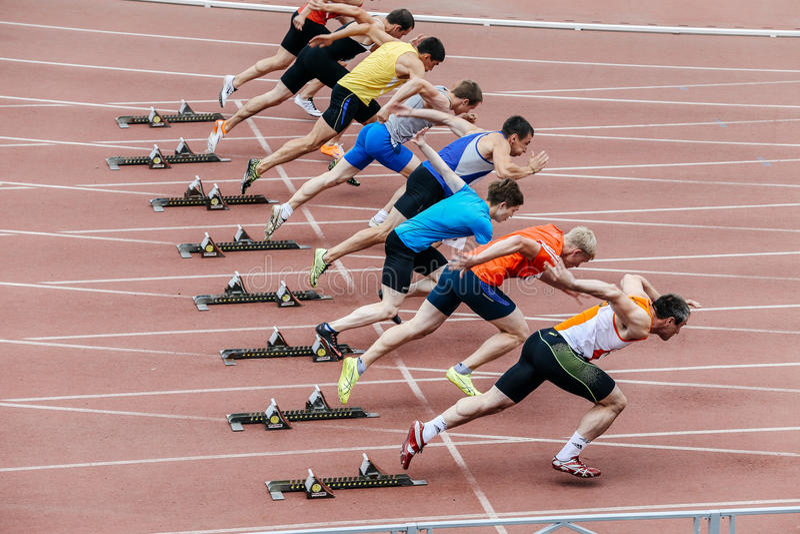 Comece atletas dos homens em uma distância da sprint de 100 medidores imagens de stock royalty free