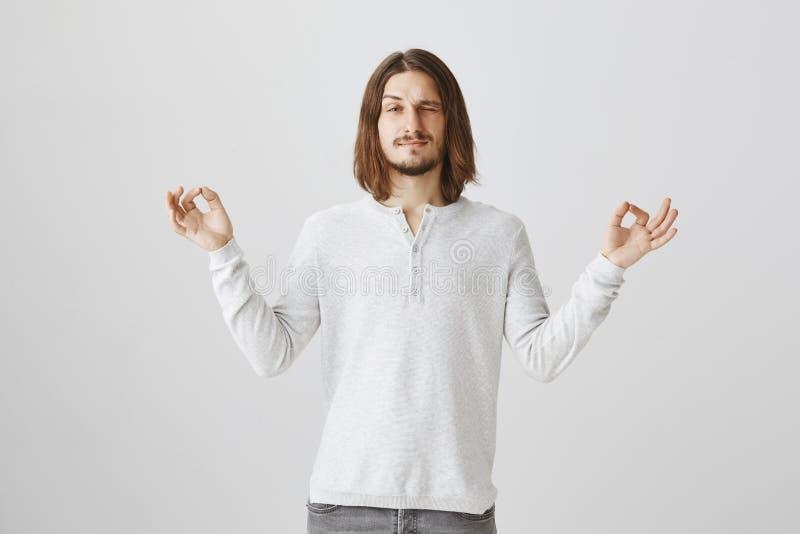 Comece seu dia com ioga O tiro do estúdio do homem delgado bonito com barba e cabelo longo espalhou as mãos com gesto do zen fotos de stock royalty free
