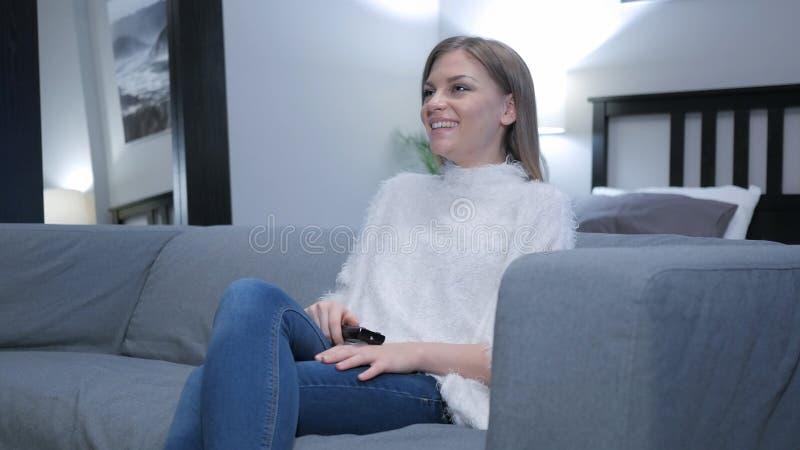 Comedia de observación de la mujer feliz en la TV foto de archivo