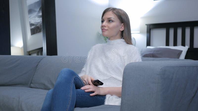 Comedia de observación de la mujer joven en la TV foto de archivo