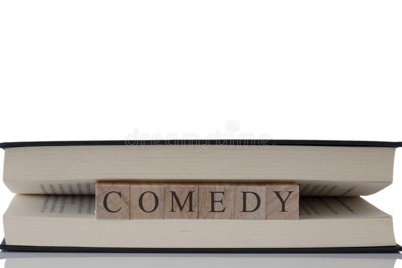 Comedia escrita en bloques de madera dentro de un libro aislado en un fondo blanco fotos de archivo libres de regalías