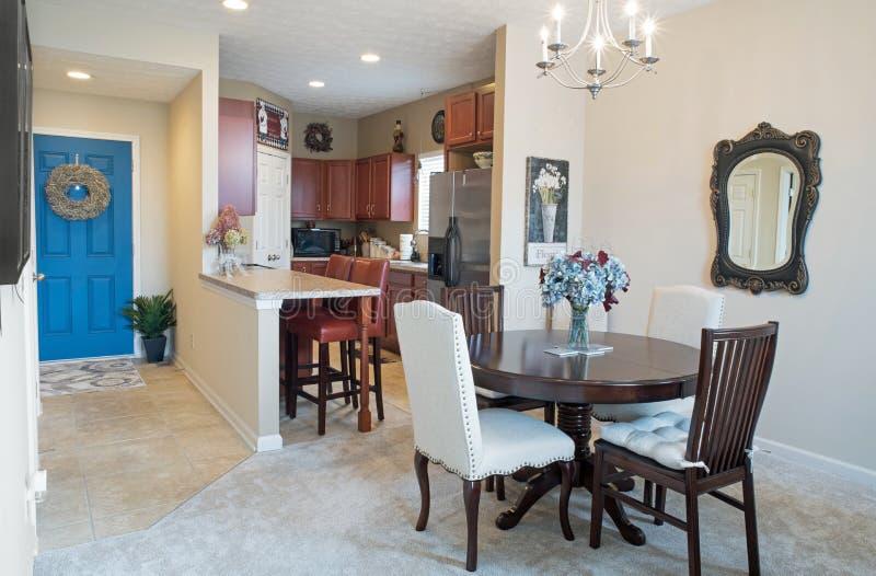 Comedor, cocina y entrada de la propiedad horizontal con la puerta azul fotografía de archivo libre de regalías