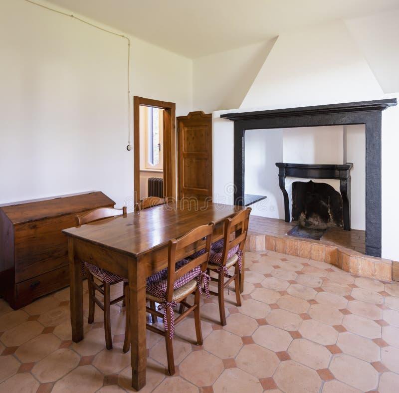 Comedor con la tabla, sillas de madera y una chimenea de piedra foto de archivo