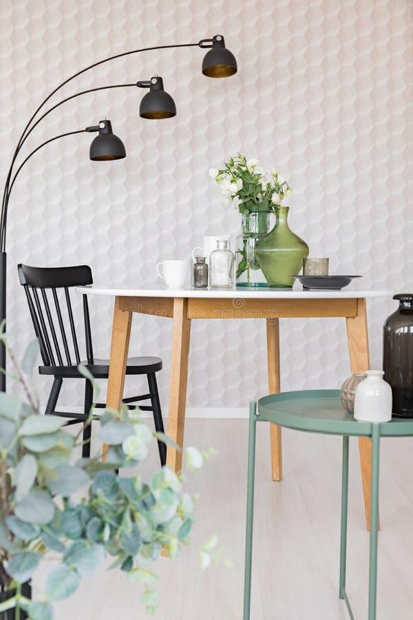 Comedor elegante con la mesa redonda con los floreros y las flores al lado de la silla de madera negra y la lámpara industrial de fotos de archivo