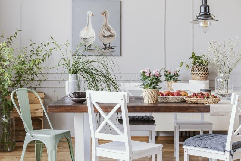 Comedor rústico con la tabla larga y las sillas blancas y pintura al óleo en la pared gris, foto real fotografía de archivo libre de regalías