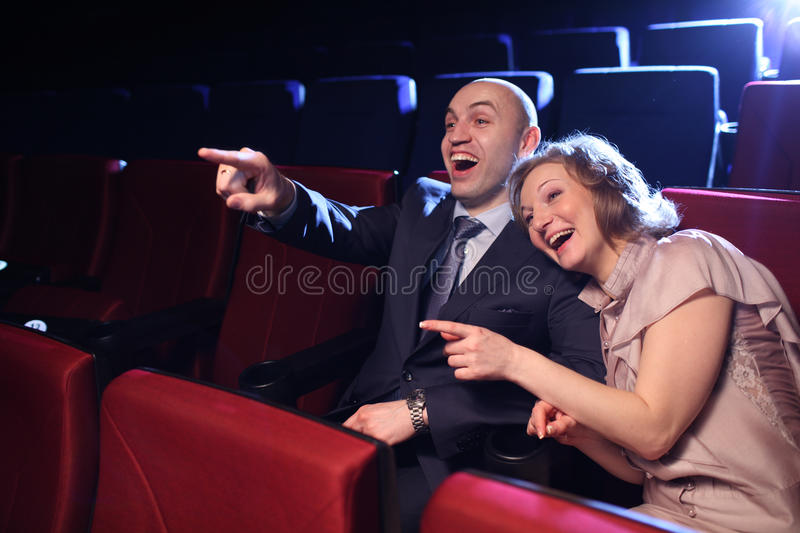 Comedy movie. Young couple in cinema movie theater laughing watching comedy show