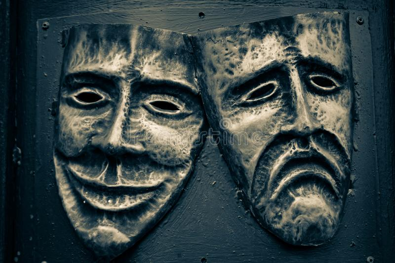 Comedy and tragedy steel masks painted in golden and dark blue colors stock photography