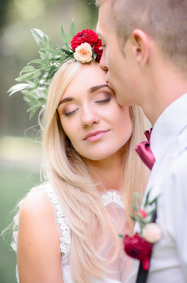 Comely bride closes her eyes while groom kisses tender her face.  royalty free stock image