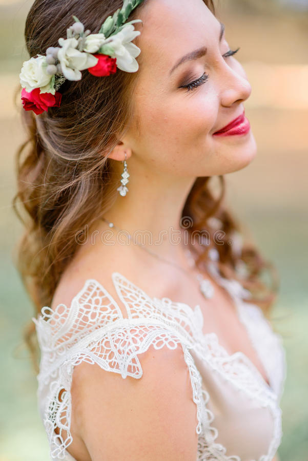 Comely bride in red wreathe closes her eyes standing outside.  royalty free stock photos