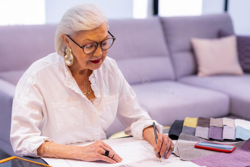Comely smiling elderly woman in glasses making designer sketch. Working boss. Comely smiling elderly left-handed woman in glasses and beautiful fancy earrings stock image